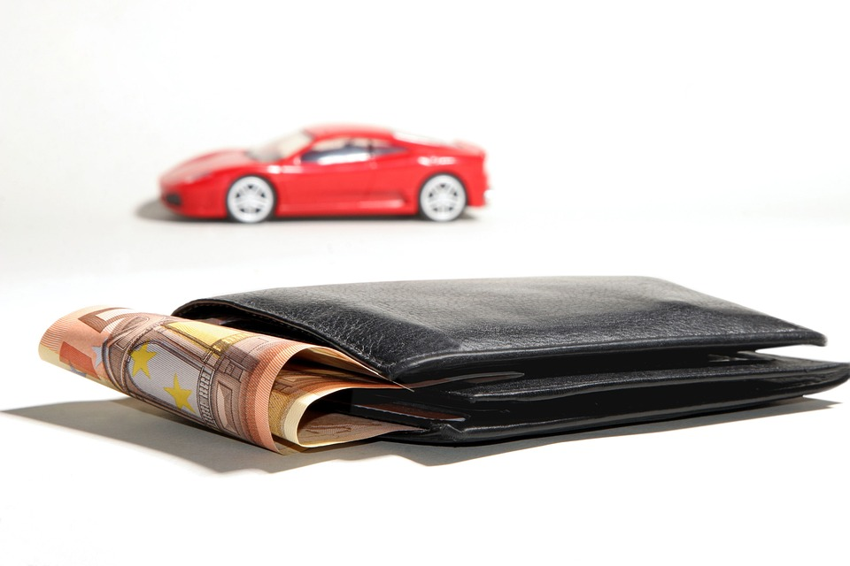 Photo of car and wallet full of money