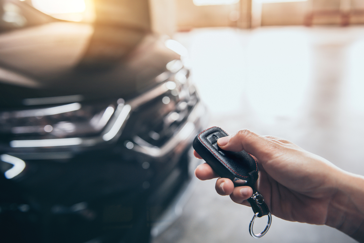 Photo of hand unlocking car with key fob