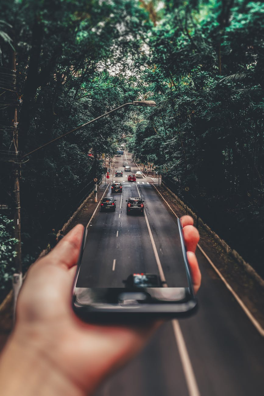 Forced perspective photo of cars driving onto road from smartphone screen