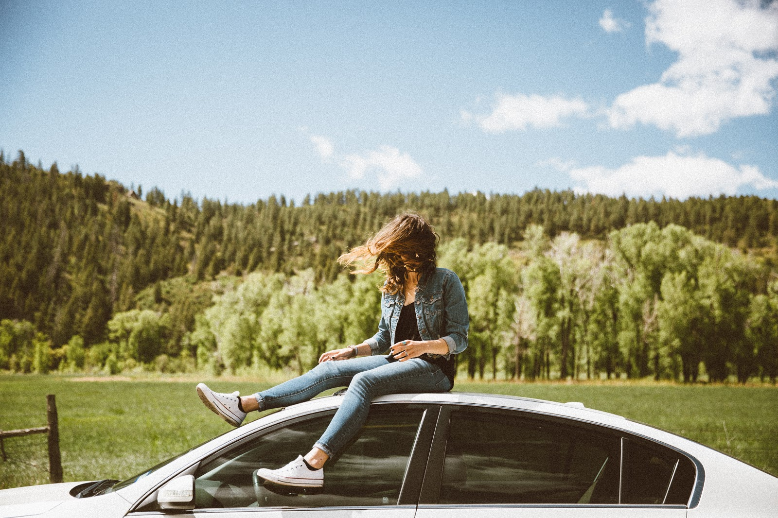 Photo of young woman sitting on top of car